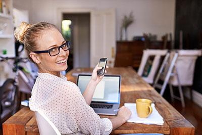 Des femmes qui prennent des notes avec leur téléphone pendant qu'elles sont assises au bureau